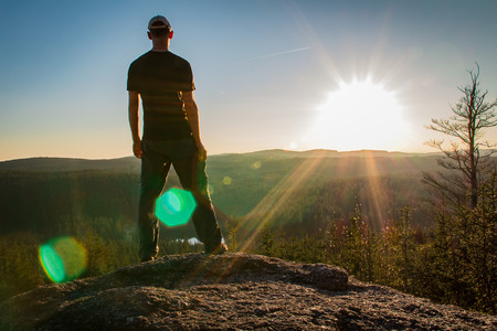 Junger Mann steht auf Felsen mit Wald und Teich und blickt ins Tal