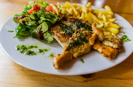 Grilled chicken steak seved with vegetables and potato chips on wood table