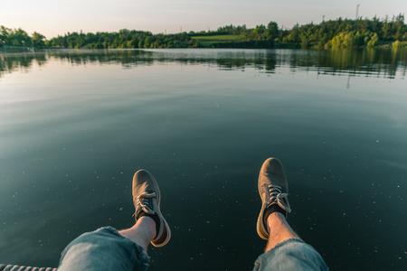 Man leg on pond Jordan at sunset in city Tabor, Czech republic 免版税图像