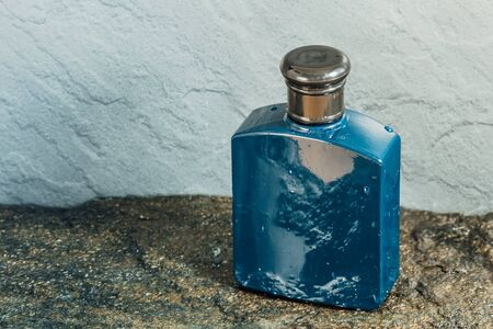 Blue aftershave bottle on wet stone texture