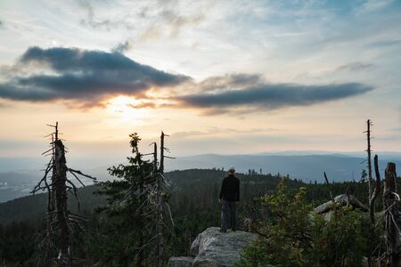 Young man tourist in white cap standing on rock at sunset in landscape, Sumava National Park and Bavarian Forest, Czech republic and Germany