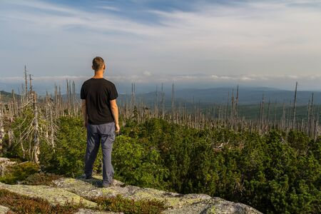 Young man tourist standing on top of mountain, Sumava National Park and Bavarian Forest, Czech republic and Germany