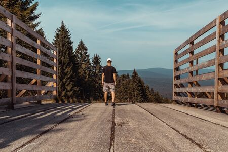 Young man standing on top of wood crossover with trees and hill, Sumava National Park, Czech republic and Germany