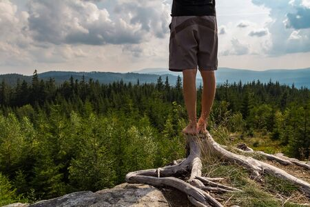 Detail of young man meditating, stretching shoeless on tree stump, Sumava national park, Czech republic