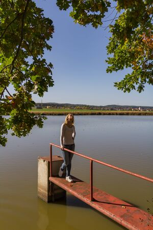 Portrait of beauty young woman standing and looking up on pond jetty, Czech autumn landscape Foto de archivo - 133516861