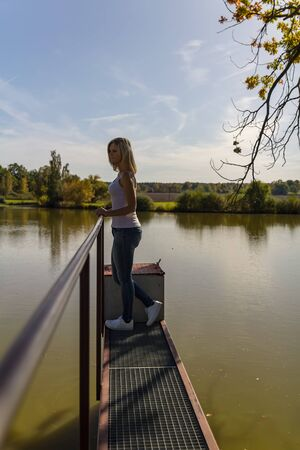 Portrait of beauty young woman from side standing on pond jetty, Czech autumn landscape Foto de archivo - 133516862