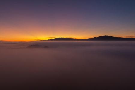 Nice autumn sunrise with misty fog and hill, Czech landscape