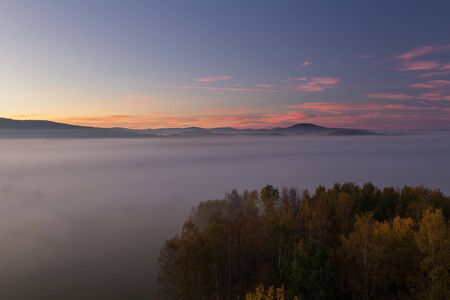Aerial view to autumn misty fog, trees and hill in sunrise, Czech landscape Reklamní fotografie