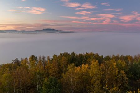 Aerial view to autumn foliage trees with misty fog and hill in sunrise, Czech landscape