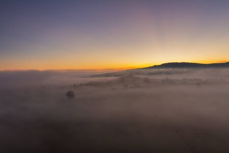 Aerial view to autumn misty fog landscape with hill in sunrise, Czech landscape