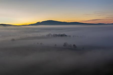 Aerial view to autumn foliage trees silhouette in misty fog and hill in sunrise, Czech landscape Reklamní fotografie