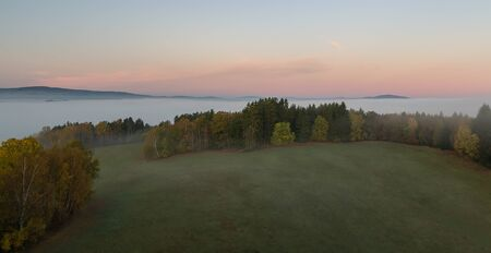 Aerial view to autumn foliage trees and meadow in misty fog and hill at sunrise, Czech landscape