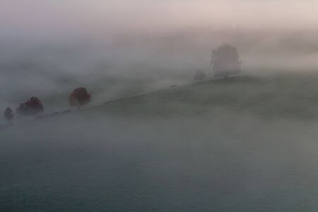 Aerial view to autumn misty trees in fog, Czech landscape