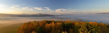 Aerial panoramic view to autumn foliage trees and meadow with misty fog and hill at sunrise, Czech landscape