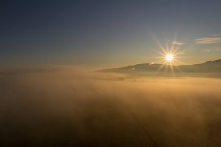 Aerial view to misty fog and hill at sunrise, Czech landscape