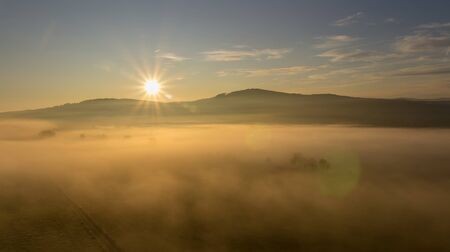 Aerial view to misty fog with path and hill at sunrise, Czech landscape
