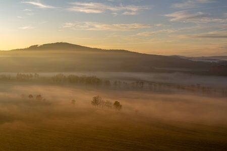 Aerial view to trees silhouette in misty orange fog at sunrise, Czech landscape