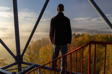 Young man standing on watchtower construction looking to autumn foliage trees with misty fog and hill at sunrise, Czech landscape