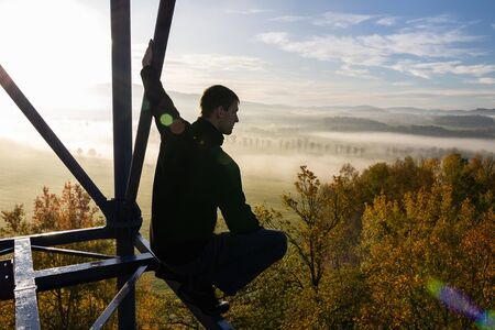 Young man sitting from side on watchtower construction looking to autumn foliage trees with misty fog and hill at sunrise, Czech landscape
