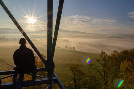 Young man sitting from back on watchtower construction looking to autumn foliage trees with misty fog and hill at sunrise, Czech landscape