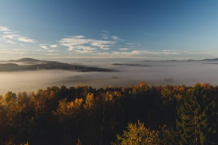 Aerial view to autumn foliage trees with misty fog and hill in sunrise, Czech landscape, toned photo Reklamní fotografie