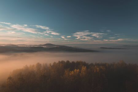 Aerial view to autumn trees with misty fog and hill in sunrise, Czech landscape, toned photo Reklamní fotografie