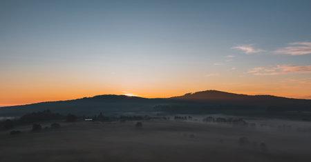 Nice autumn sunrise with misty fog on meadow and hill, Czech landscape, toned photo Reklamní fotografie