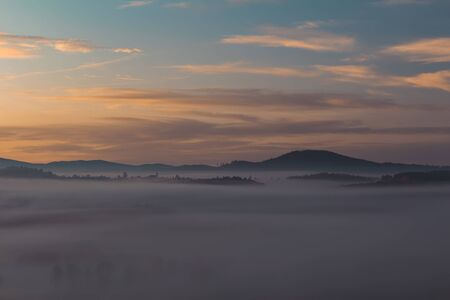 Aerial photo of autumn foliage trees with misty fog and hill in sunrise, Czech landscape