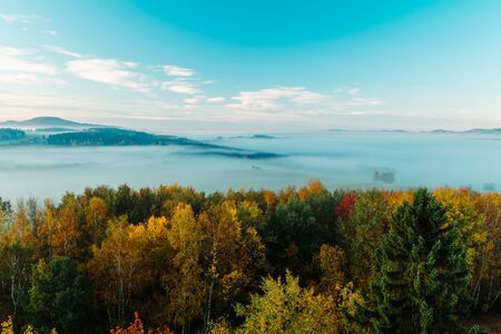 Aerial view to autumn foliage trees with misty fog, hill and blue sky in sunrise, Czech landscape, colored photo