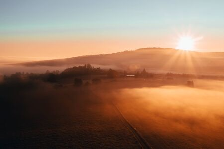 Aerial view to misty orange fog with path and hill at sunrise, Czech landscape