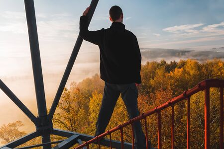 Young man standing from back on watchtower construction looking to colorful autumn foliage trees with misty fog and hill at sunrise, Czech landscape Reklamní fotografie