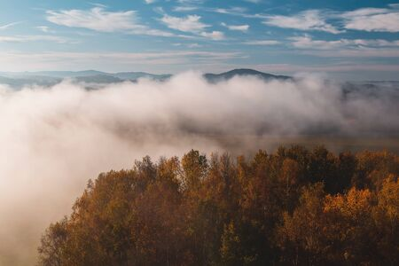Aerial view to autumn trees with misty fog and hill in sunrise, Czech landscape, colored photo Reklamní fotografie