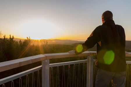 Young man standing on lookout Nebelstein, enjoy view to nature
