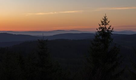 Sunset on lookout Nebelstein with trees and distant hill, Austria landscape