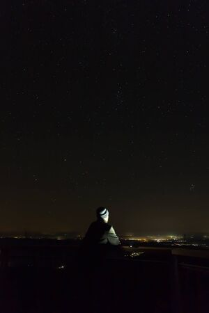Young man looking to night sky full of stars with distant city, long exposure, Austria landscape
