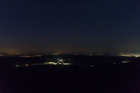 Night sky with stars and distant city, long exposure, Austria landscape