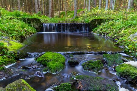 Small weir on brook in forest, long exposure photography, Czech landscape