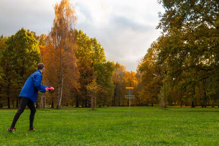 Young caucasian man in blue jacket playing disc golf on autumn play course with basket