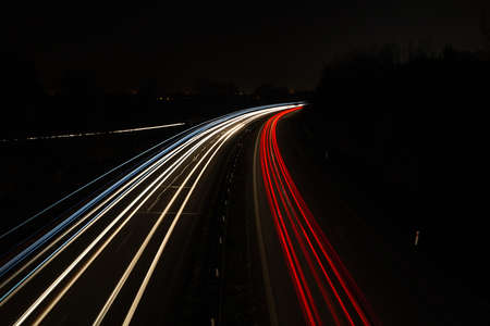 Vehicle car light trails on highway in red and white color. Trafic at night, long exposure