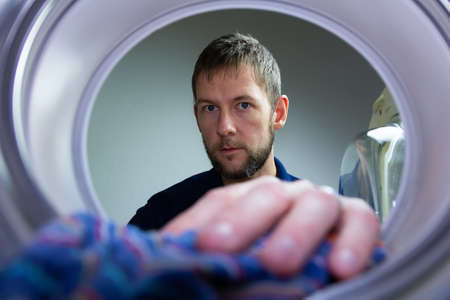 Young caucasian man take clothing out from washing machine. Man making houseworks Stockfoto