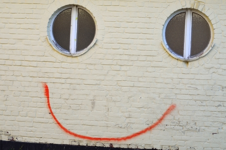 two face: A smile in the spring face graffiti on a wall with little effort by a line between two windows a smile brought to the wall Despite Schmierereii it prepares a smile
