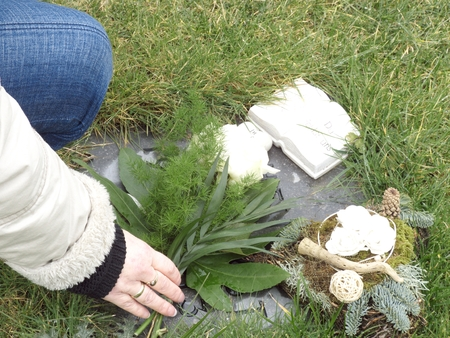 memorial candle: Hands of a woman stores the flowers on the grave