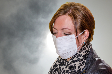 Young woman with mouth protection, respiratory protection mask against the Smoke in the city  photo
