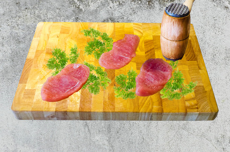 Three cutlet on a wooden board with parsley be knocked flat  photo