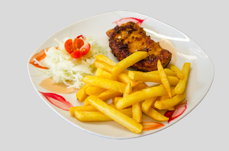 White plate with floral pattern on a schnitzel with chips and salad against white background photo