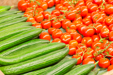 Various tomatoes and cucumbers for sale at a farmers market