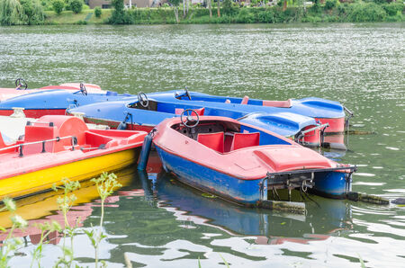 dysentery: Red blue pedal boats at the dock for hire on the Ruhr reservoir in Essen Kettwig