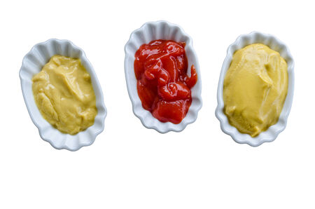 Close up of ketchup and mustard on three small white plates  photo