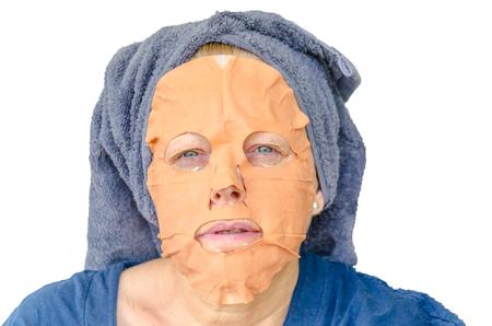 alumina: Woman with facial mask consisting of a clay mixture.