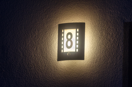 Illuminated house number, outdoor lamp with integrated number 8 at night on a white wall.